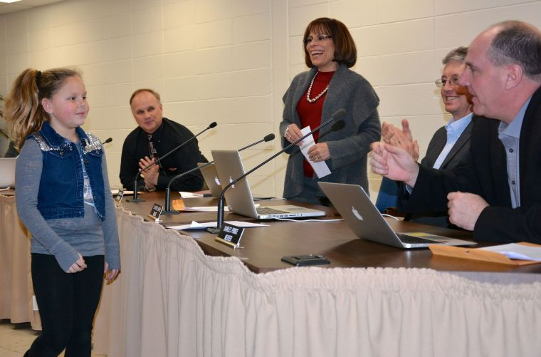 """After presenting the Dixon Valve & Coupling Co. donation to Superintendent Karen Couch, on Jan. 13, Worton Elementary School student Keira McColigan greets the Kent County Board of Education members. From right are: Charles """"Chic"""" Prince, Michael Harvey, Couch and President Bryan Williams. The other members are Vice President Jeff Reed and Brian Kirby."""